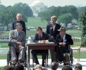 This photo depicts George H.W. Bush signing the ADA into law, with Evan Kemp on the left and Justin Dart on the right.