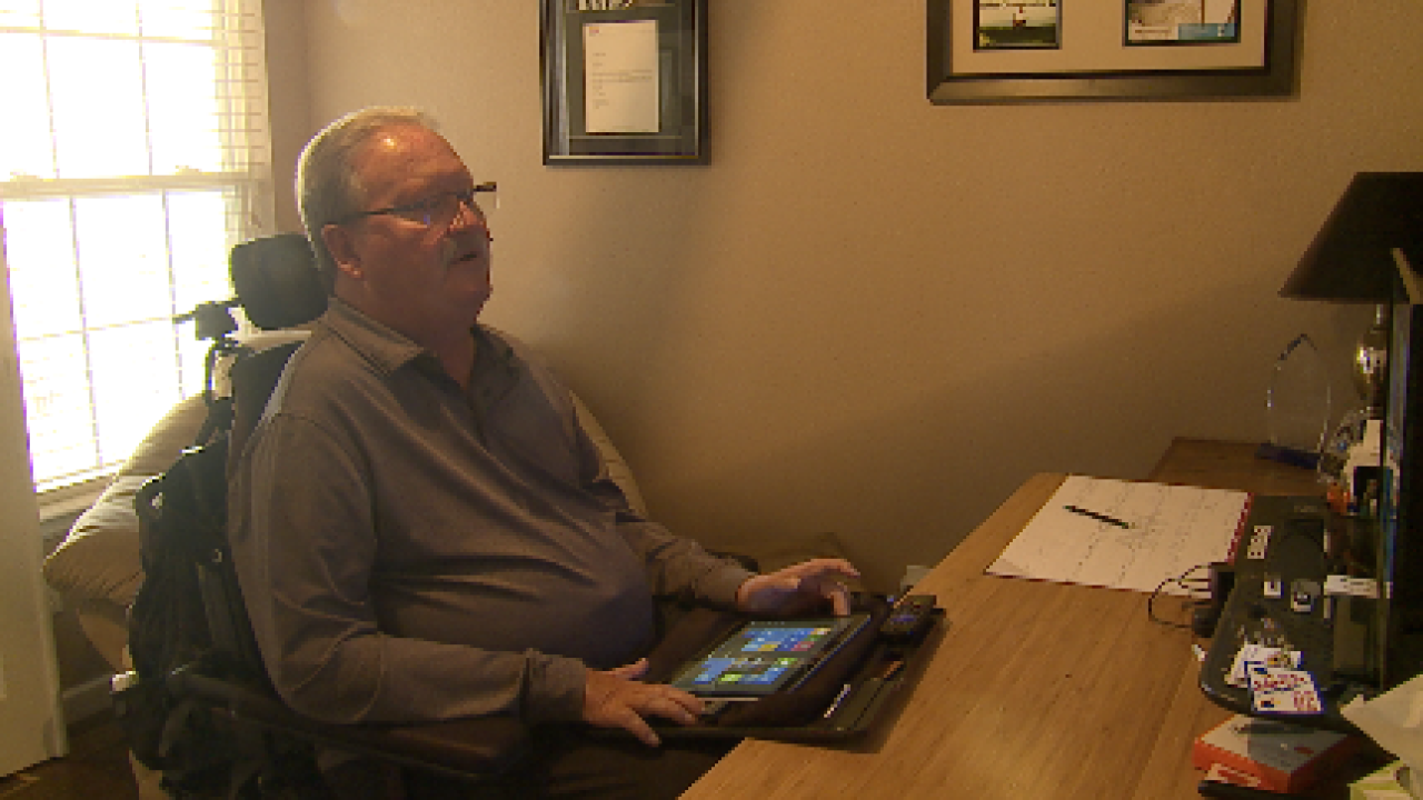 Picture of Curt Wolff working on his desk, using a tablet