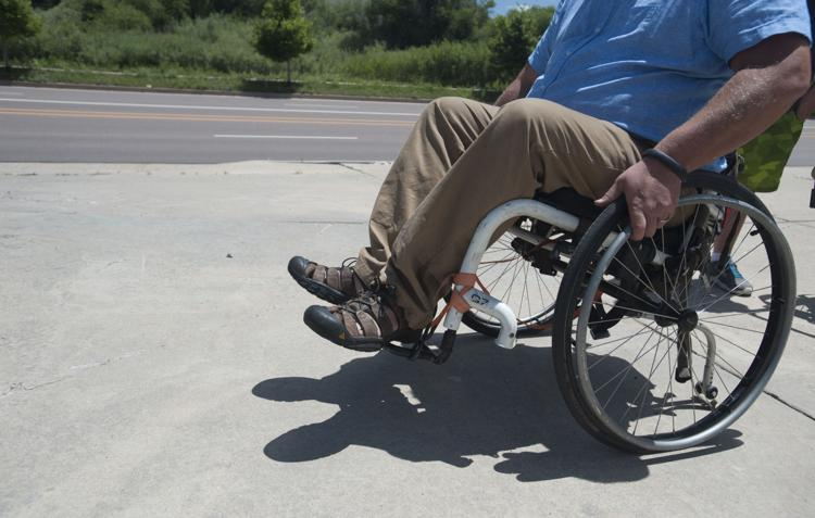 Picture of a man in a manual wheelchair doing a wheely