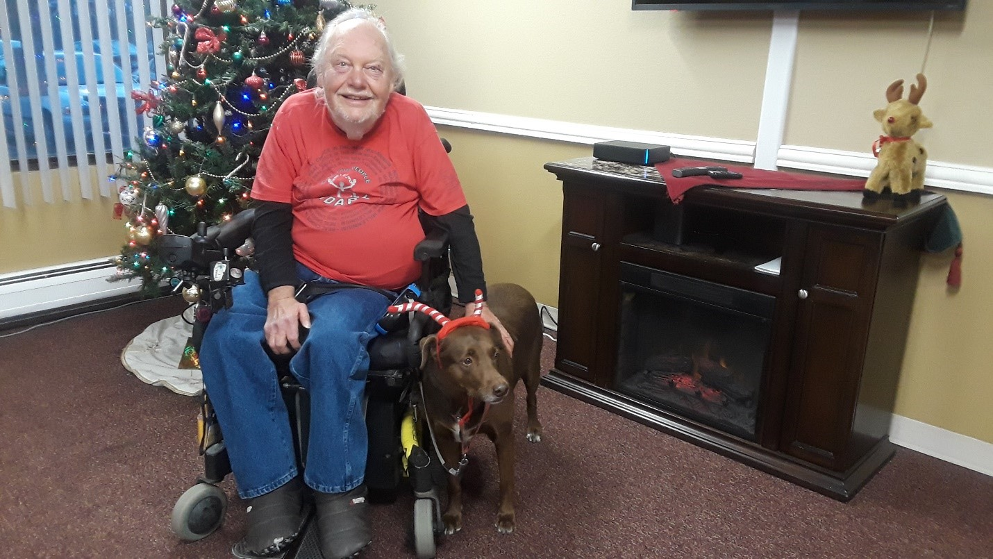 Picture of CCDC's former accountant, currently a volunteer, and his service dog Hershey in front of his Christmas tree