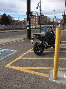Picture of motorcycle parked in yellow crosshatched access aisle adjacent to accessible parking space