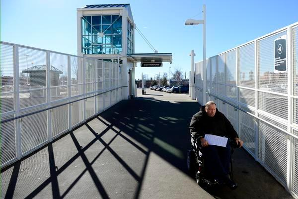 John Barr, crossing an RTD bridge in a power wheelchair