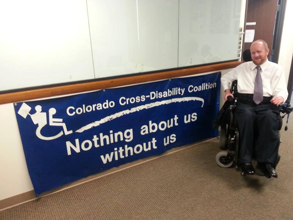 "Picture of Kevin W. Williams, CCDC Civil Rights Legal Program Director shown in front of banner that reads, ""Colorado Cross-Disability Coalition: Nothing about us without us."""