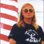Image of Wade Blank, standing in before an American flag