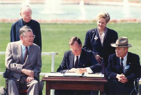 "Image of President George H.W. Bush with Evan J. Kemp, Jr., then the chairman of the Equal Employment Opportunity Commission (pictured next to President Bush seated in his motorized wheelchair) and Justin Whitlock Dart, Jr., often called the ""Godfather of the ADA,"" an American activist and advocate for people with disabilities and co-founder of the American"