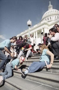 """Capitol Crawl"" photo of protesters with disabilities crawling up the Capitol steps in Washington, DC to protest the lack of accessibility and get the Americans with Disabilities Act passed."