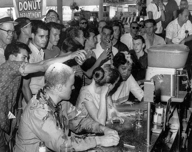 "Image of the young, Black student, Anne Moody ""sitting-in"" at an ""All Whites"" lunch counter being taunted and tormented by many young white people expressing disapproval. Photo courtesy of the Jackson Free Press."