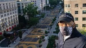 "John Lewis observing Black Lives Matter Plaza in Washington, D.C., where the words ""BLACK LIVES MATTER"" are painted in large yellow letters on 16th St. in Washington, D.C. John Lewis wearing a facial mask and a baseball cap that reads ""1619,"" courtesy of ""How the Black Lives Matter generation remembers John Lewis,"" KSTP.com"