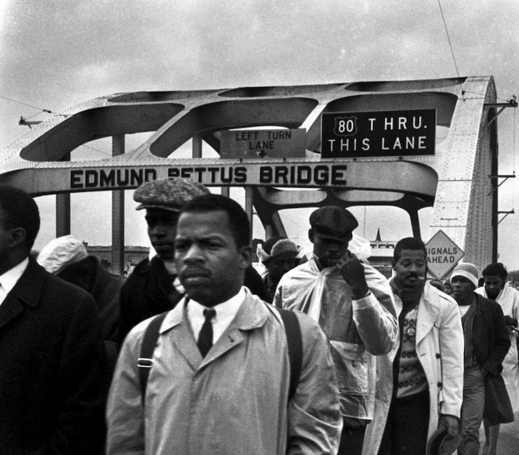 "Image of young John Lewis as he proudly crosses Edmund Pettus Bridge, leading the March on Bloody Sunday to secure voting rights for Black Americans in the state of Alabama. Photo from ""There's a better way to honor John Lewis than renaming the Edmund Pettus Bridge"" AL.com, Alabama."