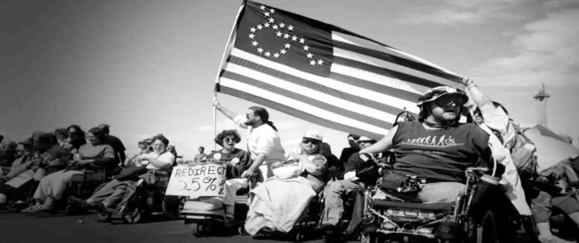 Picture of Activist of ADAPT, raising the U.S. flag with the disability symbol formed by stars