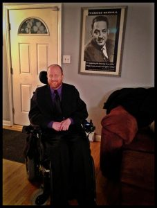 Photograph of Kevin Williams sitting in front of framed poster of Thurgood Marshall next to the front door of his home