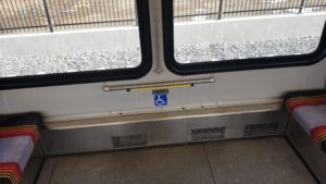 Photograph of RTD new light rail accessible seating location arrangement with accessibility symbol on floor